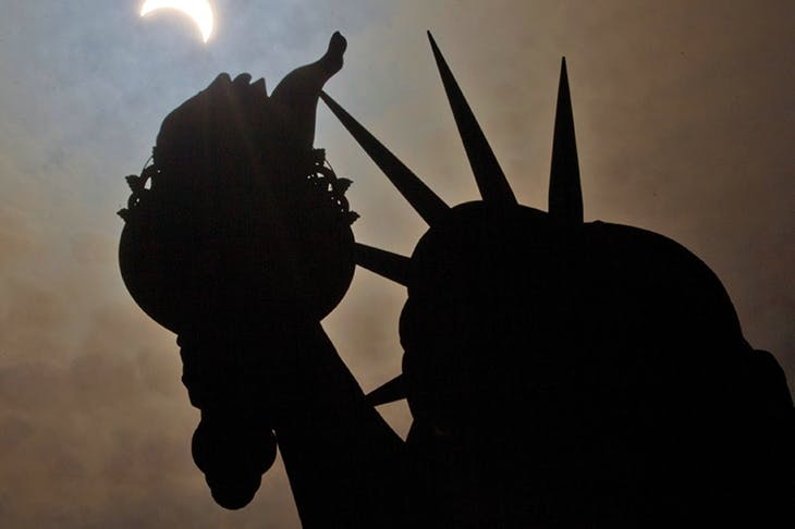 The Statue of Liberty, photographed during a partial solar eclipse. 'Far from being a cheerful present from one nation to another, Liberty is a subversive and occult statement'
