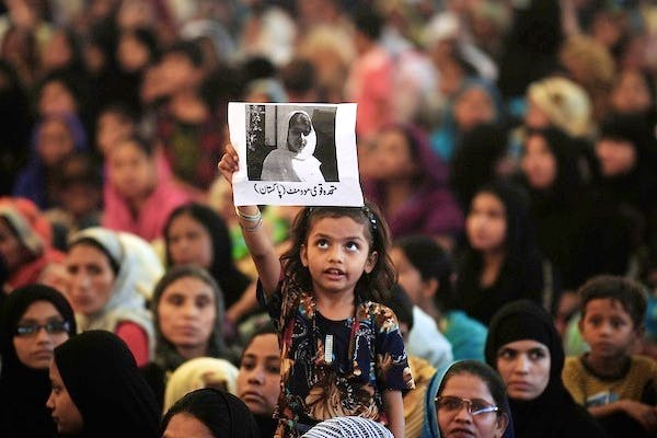 A Pakistani female supporter of Muttahida Quami Movement carries a photograph of gunshot victim, Malala Yousufzai. Picture: Getty