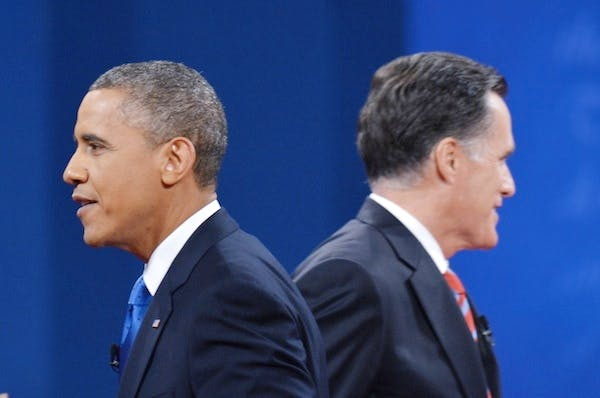 US President Barack Obama Republican presidential candidate Mitt Romney make their way to greet their wives at the end of the third and final presidential debate. Picture: Getty
