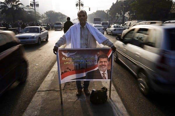 A Mursi supporter holds a banner as hundreds of others protest against the President's decision to grant himself sweeping new powers. Picture: Getty