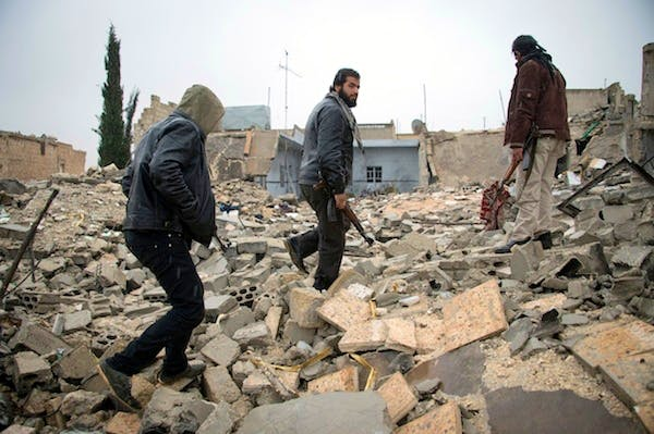 Rebel soldiers walk through the rubble of building in the northern Syrian city Aleppo today. Picture: Getty