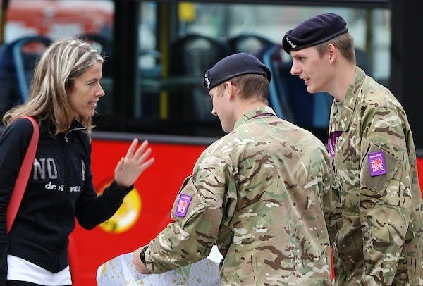 Two members of the military direct a woman during the Olympic Games. Picture: Getty