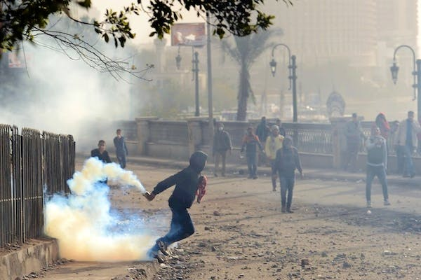 An Egyptian protester prepares to throw back a tear gas canister fired by riot police during clashes near Cairo's Tahrir Square yesterday. Picture: Getty