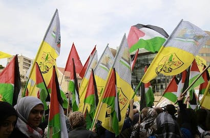 A Lebanese protestor waves the Hezbollah flag and the Palestinian flag during a protest. Picture: Getty
