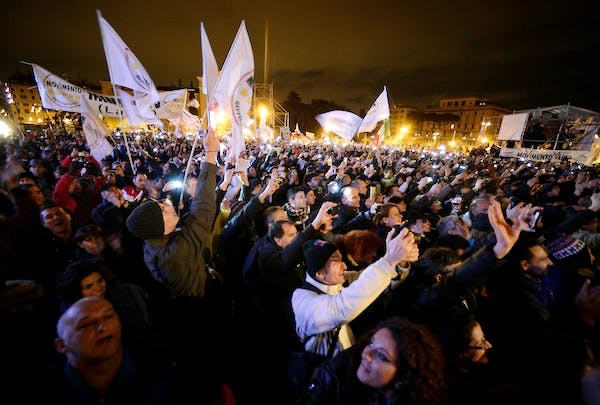 Supporters cheer comedian-turned-political agitator, Beppe Grillo, as he arrives for his final rally in Rome. Picture: Getty