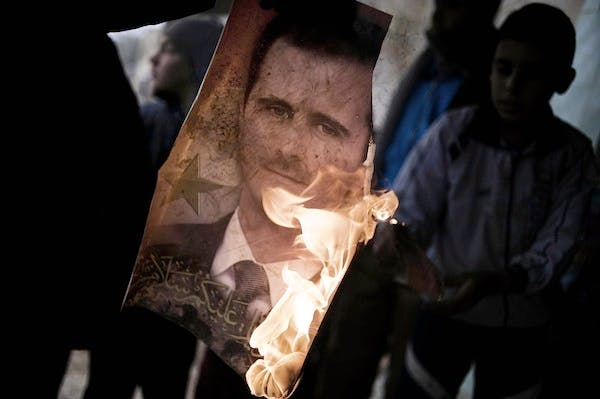 A member of the Free Syrian Army holds a burning portrait of embattled President Bashar al-Assad. Picture: Getty