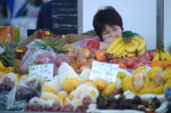 A fruit seller waits for customers in a wet market in Shanghai. China's economic growth slowed to 7.7 percent in the first quarter, data showed. Picture: Getty