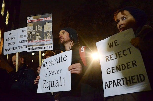 Protesters at a rally in Tavistock Square hold placards rejecting gender segregation. Picture: PA